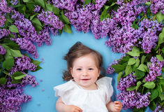Pretty little girl lying on blue background with lilac flowers Royalty Free Stock Photography