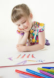 Pretty little girl lying on the floor and looking on her drawing Stock Photos