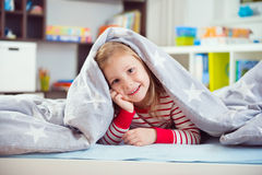 Pretty little girl lying under blanket Stock Images