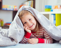 Pretty little girl lying under blanket Royalty Free Stock Photography