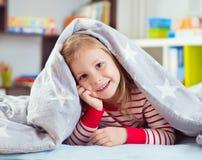 Pretty little girl lying under blanket Royalty Free Stock Photography