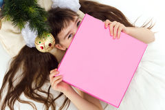 Pretty little girl lying under a Christmas tree. With present Royalty Free Stock Photo