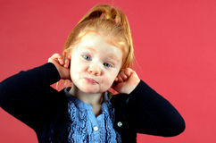 Pretty little girl making funny face. Little redhead girl with blue eyes holding her ears and making funny face Royalty Free Stock Photography