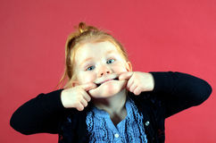 Pretty little girl making funny face. Little redhead girl with blue eyes making funny face Stock Photos