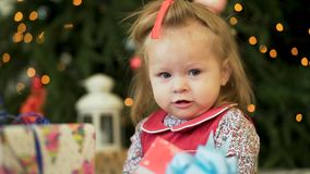 Pretty little girl near the new year tree. Little girl smiles and play with gifts on the background of Christmas trees royalty free stock photography