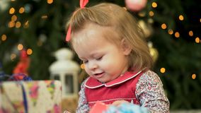 Pretty little girl near the new year tree. Little girl smiles and play with gifts on the background of Christmas trees stock photos
