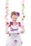 Pretty little girl near pink floral swing isolated Royalty Free Stock Images