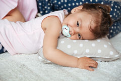 Pretty little girl with nipple lies on bed with mother Stock Images
