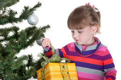Pretty little girl is opening a christmas gift Royalty Free Stock Image