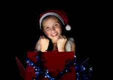A pretty little girl opens her Christmas present Stock Photography