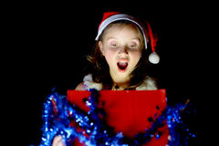 A pretty little girl opens her Christmas present Stock Photo