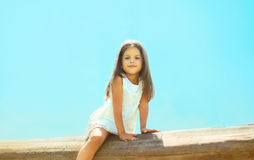 Pretty little girl outdoors, blue sky. Summer day Royalty Free Stock Photography