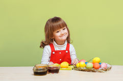 Pretty little girl paints eggs Royalty Free Stock Photo