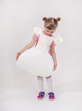 Pretty little girl in a paper dress. Neutral background Royalty Free Stock Photo