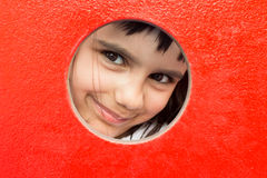 Pretty little girl peeking through a hole. In a playground stock photography