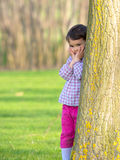 Pretty little girl peeking out from behind a tree in the park Stock Photography