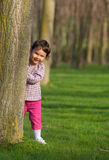 Pretty little girl peeking out from behind a tree in the park Royalty Free Stock Photography