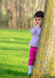 Pretty little girl peeking out from behind a tree in the park Royalty Free Stock Images