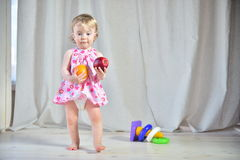 Pretty little girl in a pink dress with red apple and orange Stock Photos