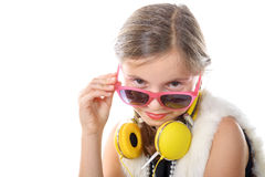 A pretty little girl with pink glasses and yellow headphones Stock Photos