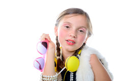 A pretty little girl with pink glasses and yellow headphones. On white background Royalty Free Stock Images
