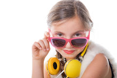 A pretty little girl with pink glasses and yellow headphones Royalty Free Stock Photography