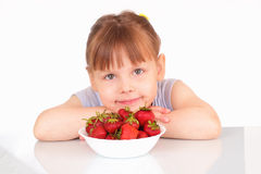 Pretty little girl and plate with strawberries Stock Photos