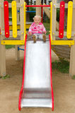 Pretty little girl play on playground in the park. Royalty Free Stock Photos