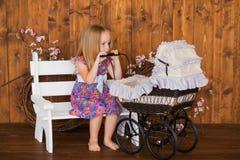 Pretty little girl play with retro pram, baby stroller Stock Photo