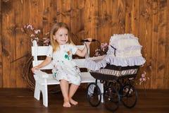 Pretty little girl play with retro pram, baby stroller Royalty Free Stock Photos
