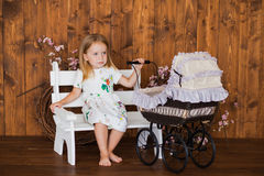 Pretty little girl play with retro pram, baby stroller Royalty Free Stock Images