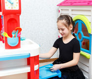 Pretty little girl play role game with toy dishes at home Royalty Free Stock Photo