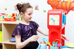 Pretty little girl play role game with toy dishes at home Stock Photography