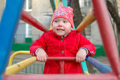 Pretty little girl on the playground monkey bars. Stock Photo