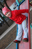 Pretty little girl on the playground slide. Stock Image
