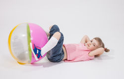 Pretty little girl playing with ball. White background Royalty Free Stock Photo