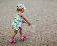 Pretty little girl is playing with big bubbles in street in summer day royalty free stock images