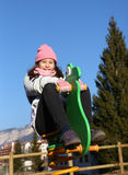 Pretty little girl playing on the carousel of a playground Stock Photos