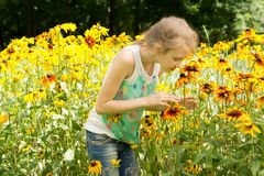 Pretty little girl playing in a colorful garden Stock Photos