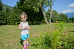A pretty little girl playing with flowers in the garden Stock Photography