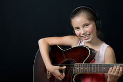 A pretty little girl playing guitar Stock Photos