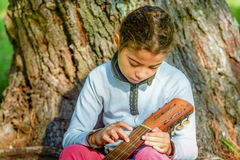 Pretty  little girl playing guitar in the park Royalty Free Stock Photo
