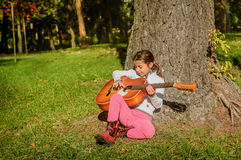 Pretty  little girl playing guitar in the park Royalty Free Stock Images