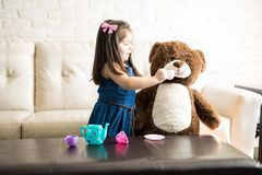 Cute little girl playing tea party with teddy bear royalty free stock images