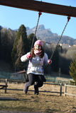 Pretty little girl is playing on a playground in the mountains Stock Photo