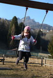 Pretty little girl is playing on a playground in the mountains Stock Photography