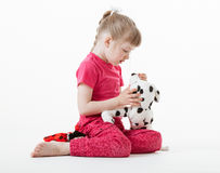 Pretty little girl playing with plush toys Stock Image