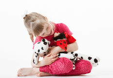 Pretty little girl playing with plush toys Royalty Free Stock Images