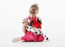 Pretty little girl playing with plush toys Royalty Free Stock Image