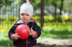 Pretty little girl playing with a red ball Stock Photo
